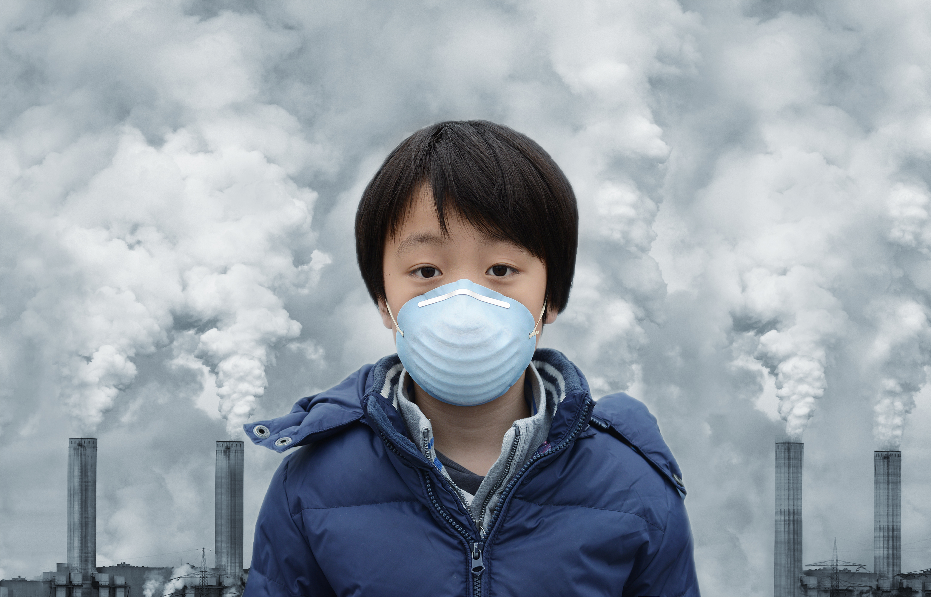 An image of a youth in front of a polluted sky.